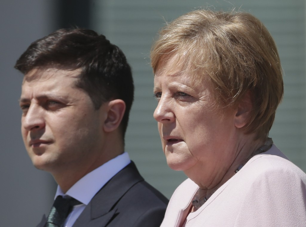 German Chancellor Angela Merkel welcomes Ukraine's President Volodymyr Zelenskiy with military honors for a meeting at the chancellery in Berlin, Germ