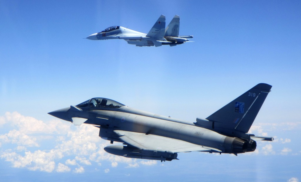 CAPTION CORRECTS AIRCRAFT NAME - In this photo  taken on Saturday, June 15, 2019, a Royal Air Force Typhoon jet, bottom, flies by a Su-30 Flanker figh...