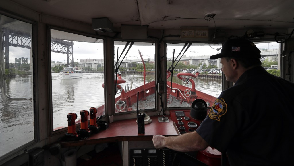 Firefighter Greg Geracioti maneuvers the Anthony J. Celebrezze down the Cuyahoga River, Thursday, June 13, 2019, in Cleveland. The fire boat extinguis