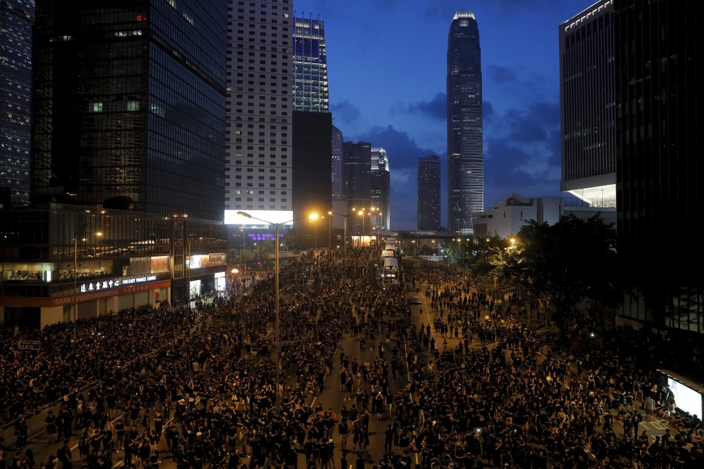 In this Sunday, June 16, 2019, photo, protesters wearing black t-shirts gather on a main road near the Legislative Council as they continuing protest