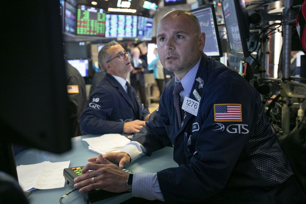 FILE- In this June 11, 2019, file photo specialist Mario Picone, right, works at his post on the floor of the New York Stock Exchange. The U.S. stock