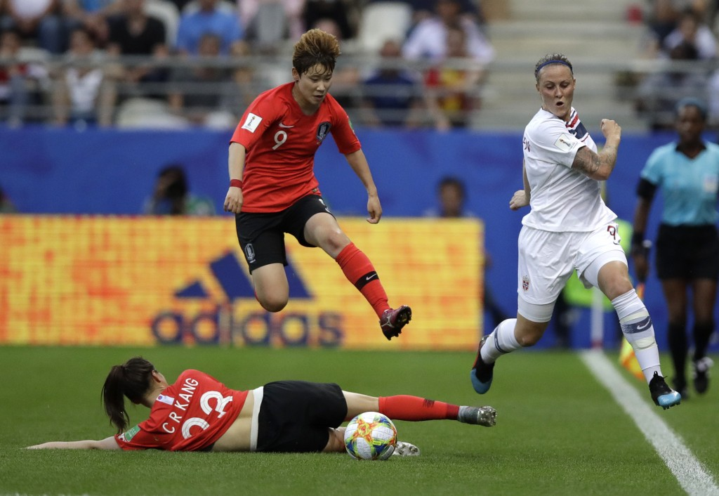 Norway's Isabell Herlovsen, right, kicks the ball clear of South Korea's Moon Mi-ra, and Kang Chae-rim, bottom, during the Women's World Cup Group A s...