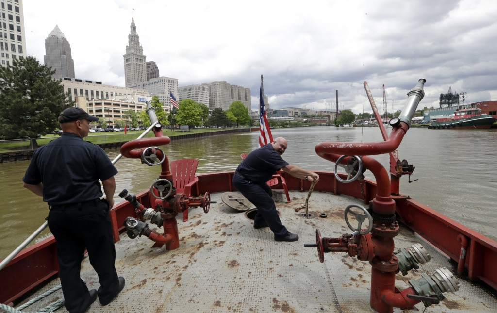 Firemen maintain the Anthony J. Celebrezze as it floats down the Cuyahoga River, Thursday, June 13, 2019, in Cleveland. The fire boat extinguished hot