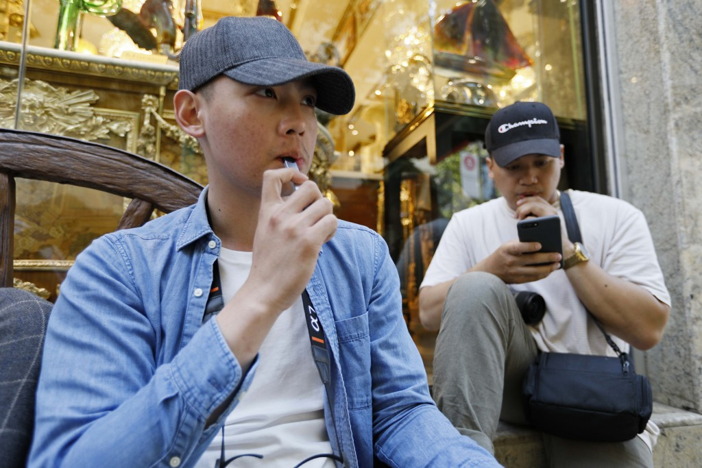In this Monday, June 17, 2019, photo, Joshua Ni, 24, and Fritz Ramirez, 23, vape from electronic cigarettes in San Francisco. San Francisco supervisor