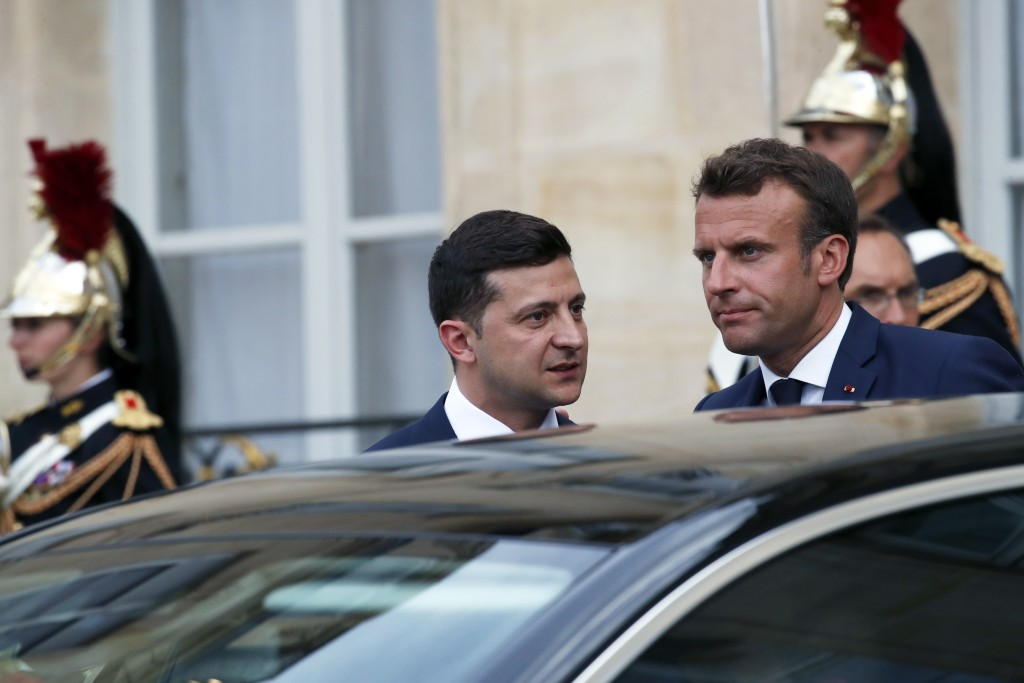 Ukrainian President Volodymyr Zelenskiy, center, leaves after a meeting with French President Emmanuel Macron at the Elysee Palace, in Paris, Monday, ...