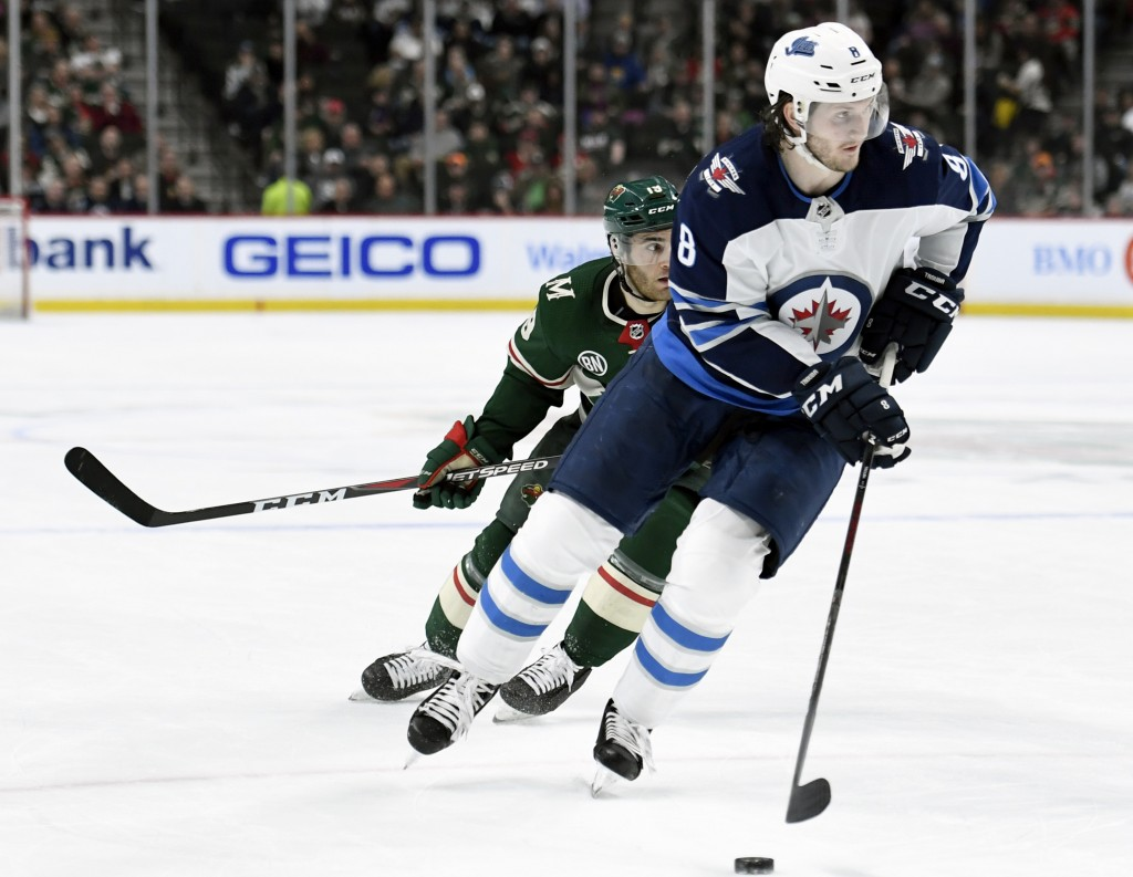 FILE - In this April 2, 2019, file photo, Winnipeg Jets defenseman Jacob Trouba (8) has the puck while shorthanded against Minnesota Wild center Luke