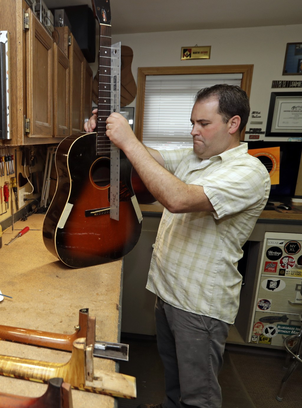 Jacob Tuel, owner of Burning River Guitars, repairs the neck on a guitar, Monday, June 10, 2019, in Akron, Ohio. Tuel named his guitar shop after the