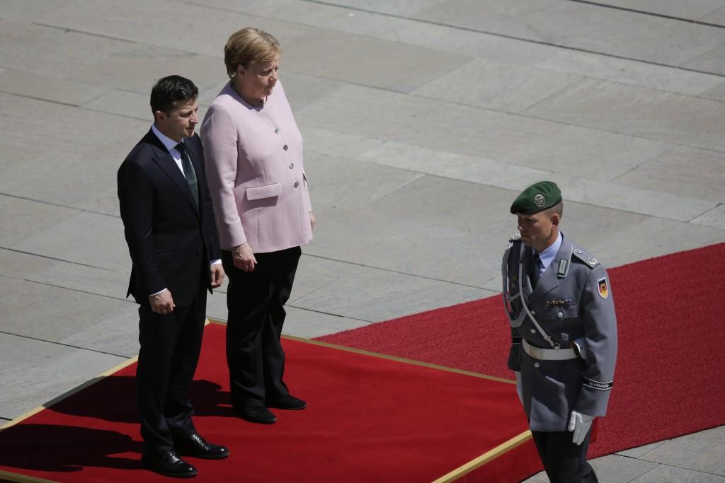 German Chancellor Angela Merkel, on the podium right, and Ukrainian President Volodymyr Zelenskiy, on the podium left, listen to the national anthems ...