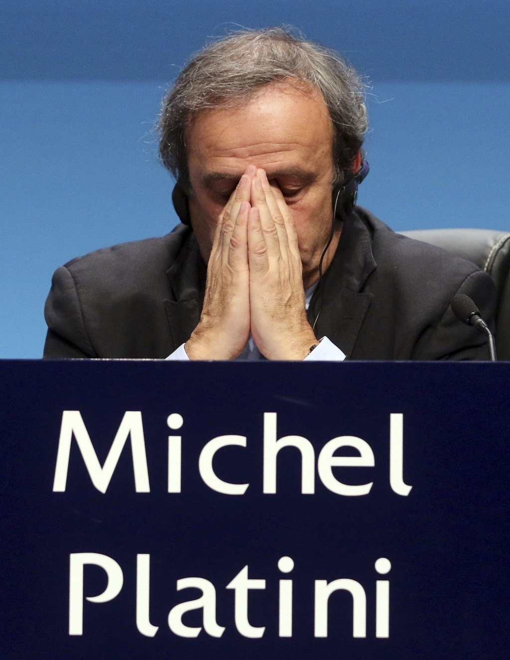FILE - In this Tuesday, March 24, 2015 file photo UEFA President Michel Platini covers his face during a news conference at the end of the 39th Ordina...