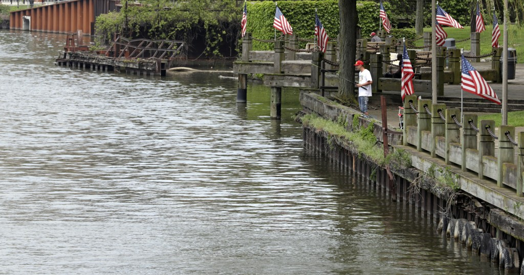 A man fishes off a dock on the Cuyahoga River, Tue...