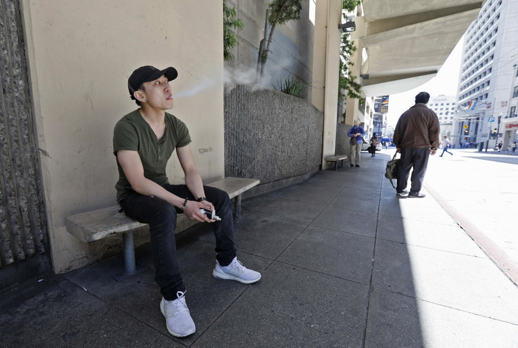 In this Monday, June 17, 2019, photo, Jacky Chan, 23, takes a vaping break from his job at a smoke shop in San Francisco. San Francisco supervisors ar