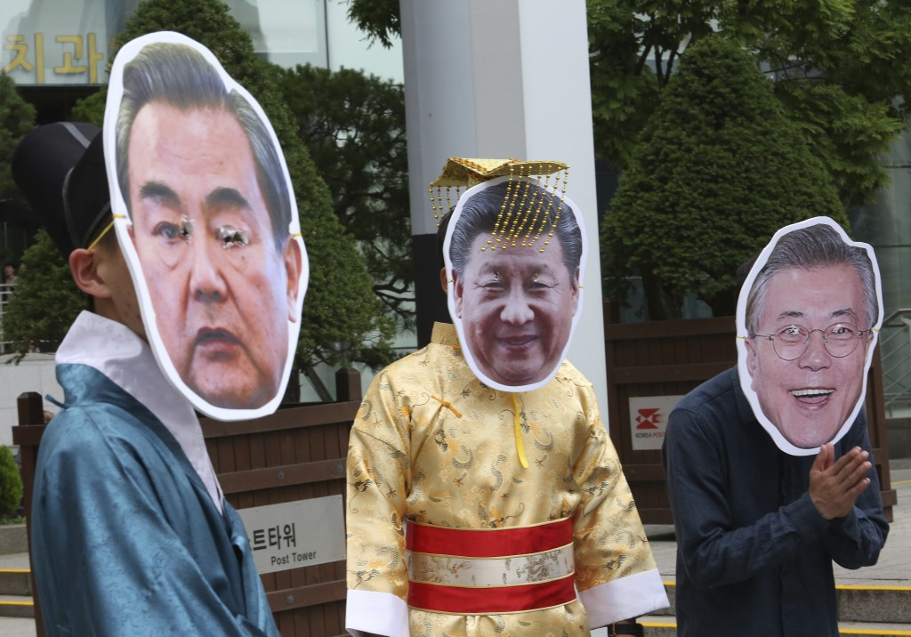 South Korean protesters wear a mask of Chinese President Xi Jinping, center, Foreign Minister Wang Yi, left, and South Korean President Moon Jae-in, r...