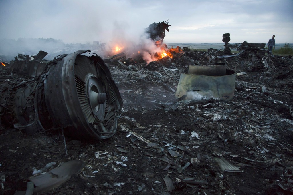 FILE - In this Thursday, July 17, 2014 file photo, a man walks amongst the debris at the crash site of a passenger plane near the village of Hrabove,