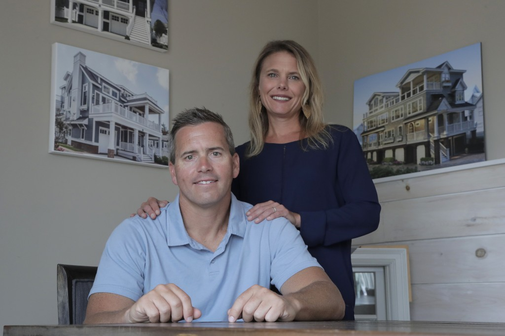In this Wednesday, June 5, 2019, photo, Chris Carr, left, president of McLaughlin Construction Management, poses for a photo with his wife Kristy Carr
