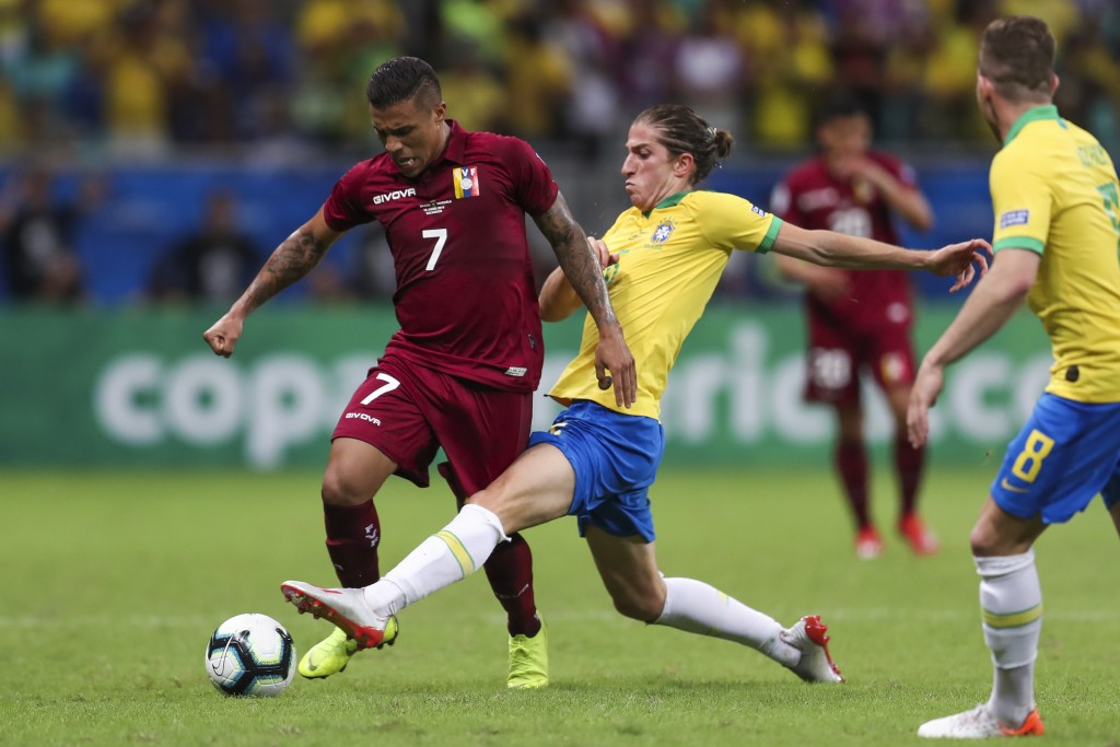 Brazil's Filipe Luis, center, vies for the ball with Venezuela's Darwin Machis, left, during a Copa America Group A soccer match at the Arena Fonte No...