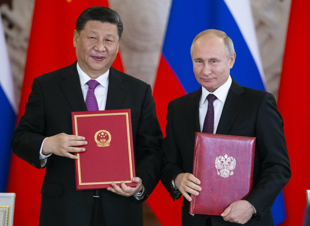 FILE - In this June 5, 2019 file photo, Russian President Vladimir Putin, right, and Chinese President Xi Jinping exchange documents during a signing