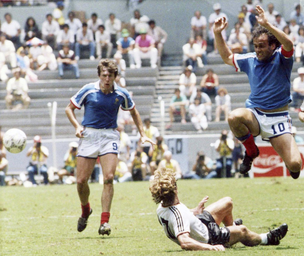 FILE - In this file photo dated June 25, 1986, France's Michel Platini, right, jumps over Germany's Ditmar Jakobs during the Football World Cup Semi-F
