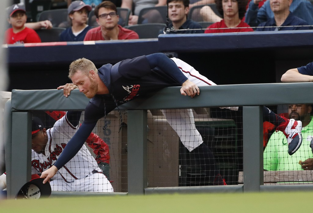 Atlanta Braves starting pitcher Mike Foltynewicz reaches over the dugout railing for a foul ball in the first inning of a baseball game against the Ne