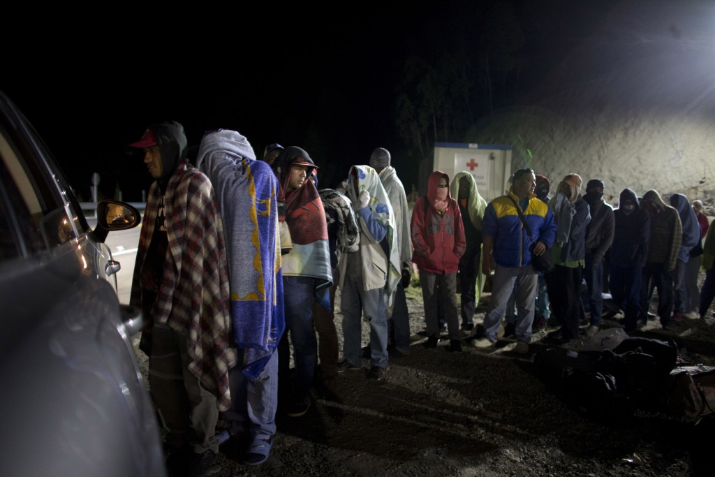 FILE - In this Aug. 31, 2018 file photo, Venezuelan migrants line up for free bread and coffee, donated by a Colombian family from their car, at a gas...
