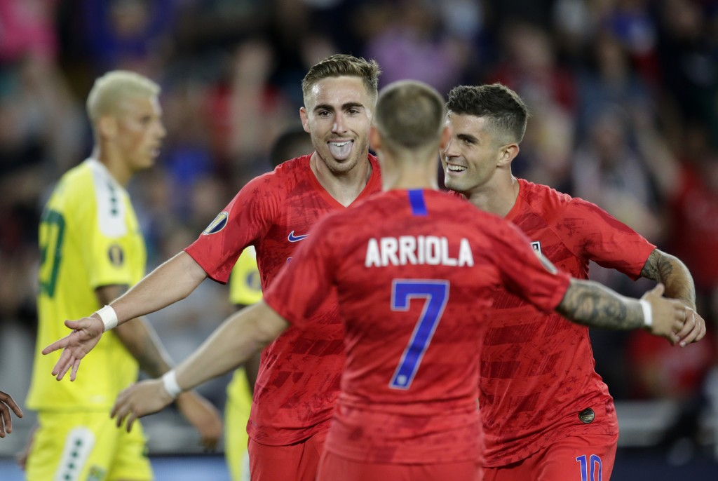 United States' Tyler Boyd, facing camera, celebrates with teammates Paul Arriola (7) and Christian Pulisic (10) as Guyana's Matthew Briggs (20) walks ...