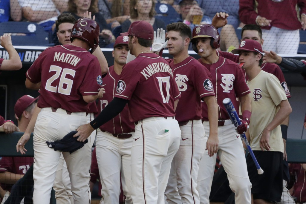 Florida State's Cole Sands (26) is greeted at the dugout after he scored a run against Texas Tech on a throwing error, in the fourth inning of an NCAA...