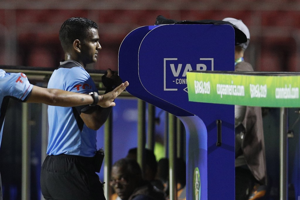 Referee Alexis Herrera reviews a play on the VAR stand during a Copa America Group B soccer match between Colombia and Qatar at Morumbi stadium in Sao...