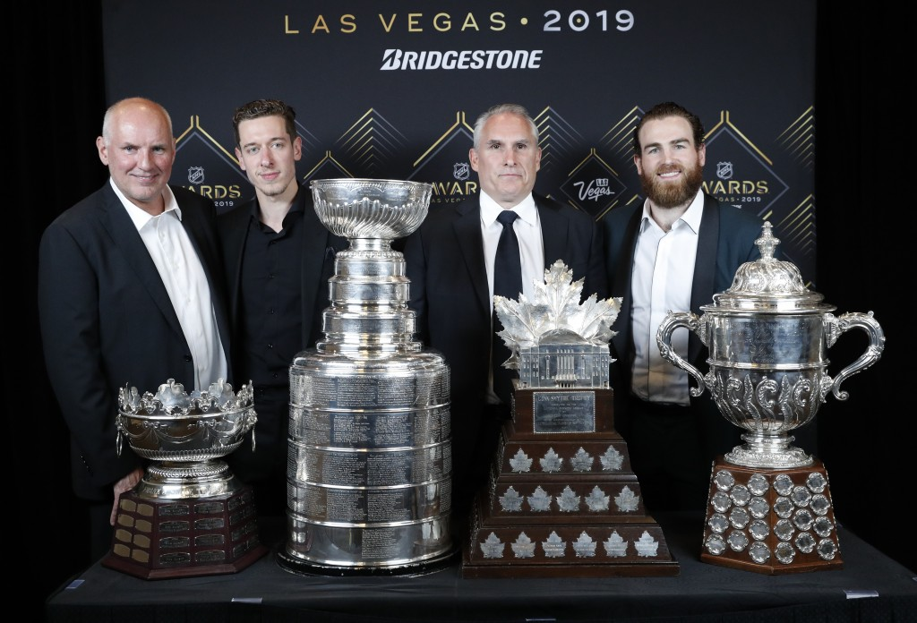From left, St. Louis Blues general manager Doug Armstrong, goalie Jordan Binnington, interim coach Craig Berube and center Ryan O'Reilly pose at the N...