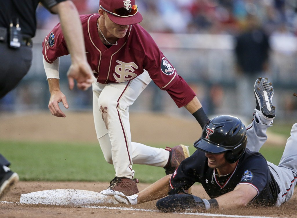 Texas Tech's Gabe Holt, right, survives a pickoff attempt by Florida State first baseman Cal Raleigh during the fifth inning of an NCAA College World ...