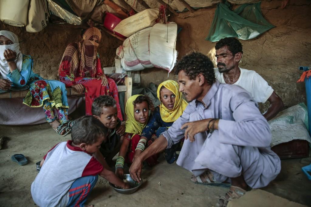 FILE - In this Oct. 1, 2018, file photo, a man feeds children halas, a climbing vine of green leaves, in Aslam, Hajjah, Yemen. The U.N. food agency ha...
