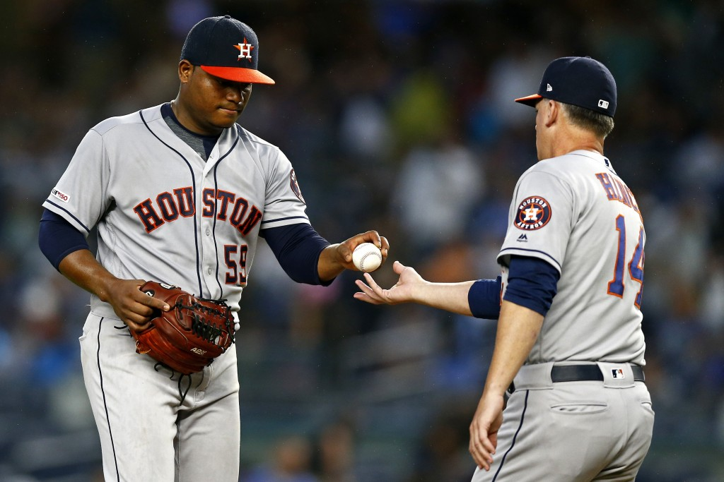 Houston Astros pitcher Framber Valdez hands the ball to manager AJ Hinch (14) during the fourth inning of the team's baseball game against the New Yor...