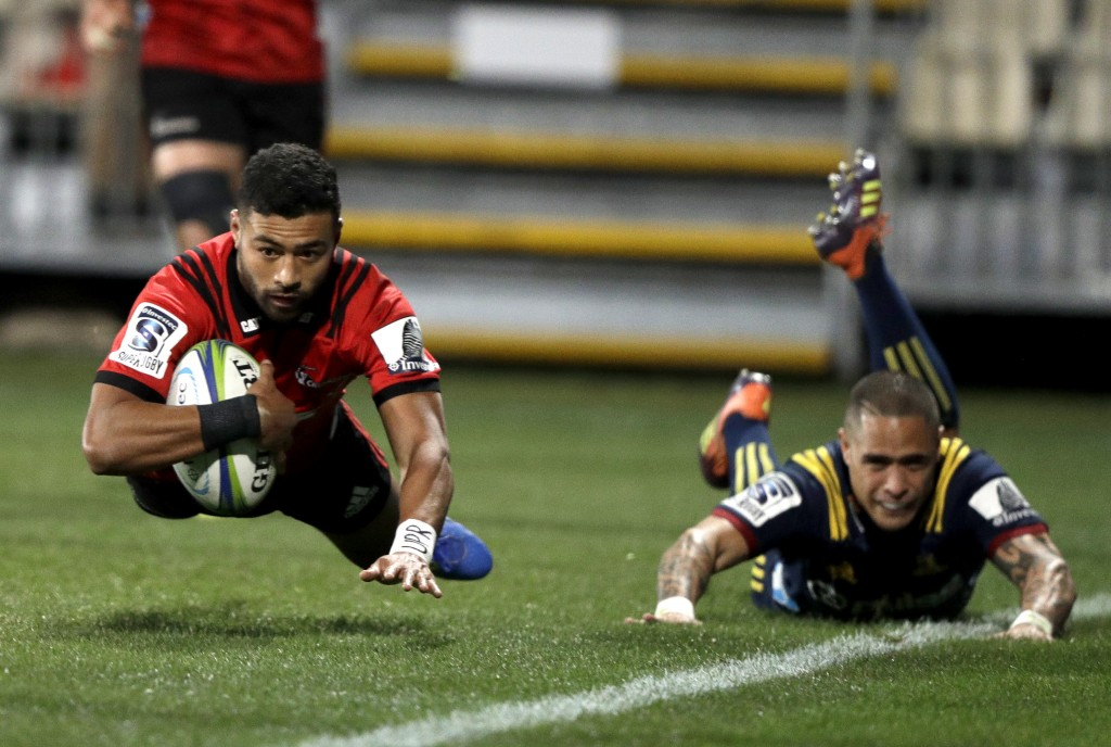 Crusaders Richie Mo'unga, left, scores his team's second try as Highlanders Aaron Smith watches during the Super Rugby quarterfinal between the Crusad...