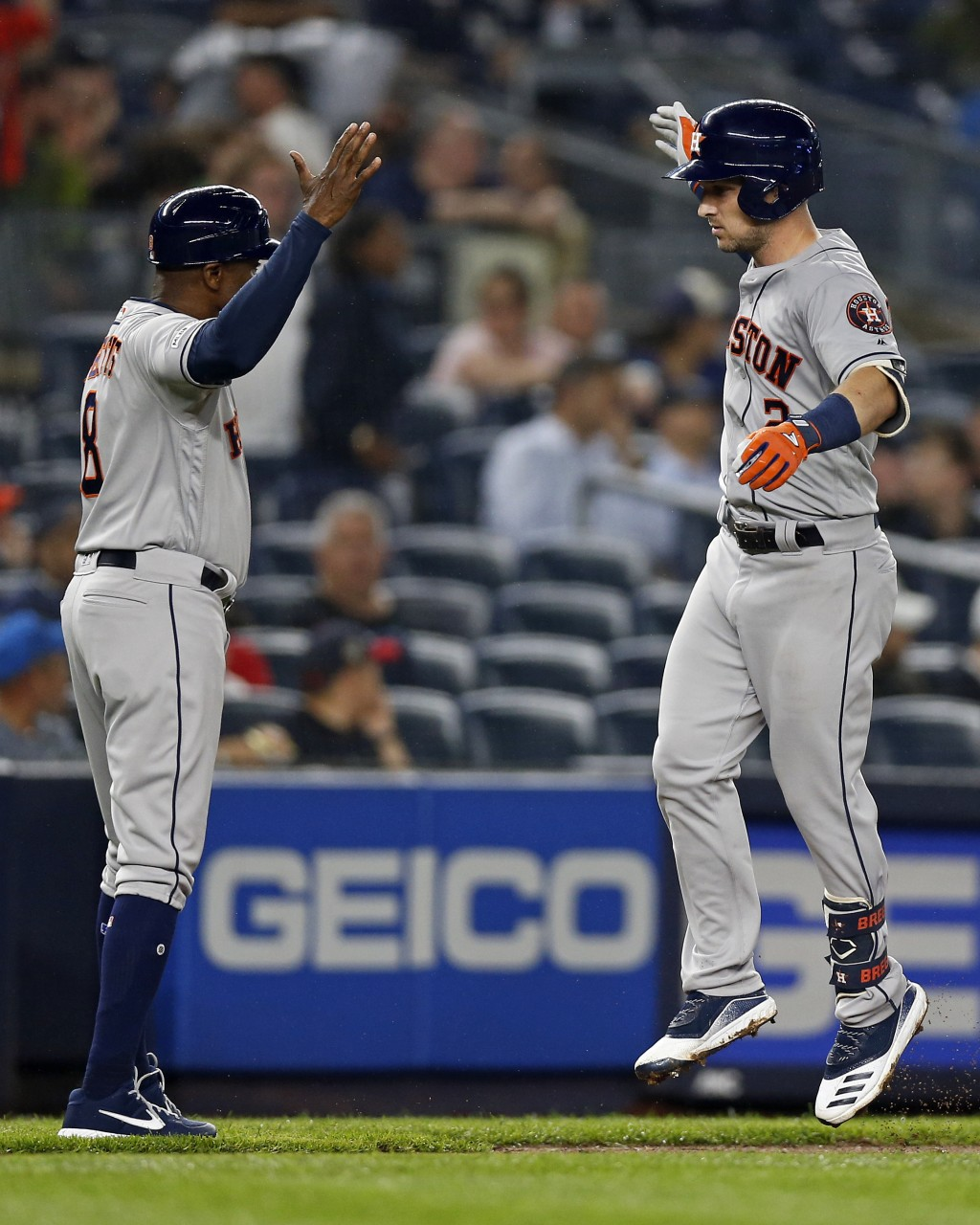Houston Astros' Alex Bregman celebrates his solo home run with third base coach Gary Pettis during the fifth inning of the team's baseball game agains...