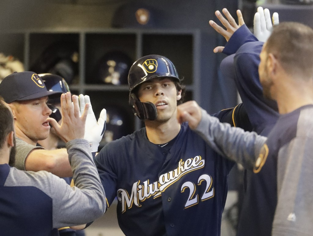 Milwaukee Brewers' Christian Yelich is congratulated after hitting a home run during the fourth inning of a baseball game against the Cincinnati Reds ...