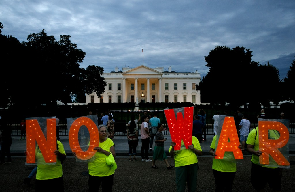 "Protesters hold signs spelling out, ""No War,"" outside the White House, Thursday June 20, 2019, in Washington, after President Donald Trump tweeted tha"