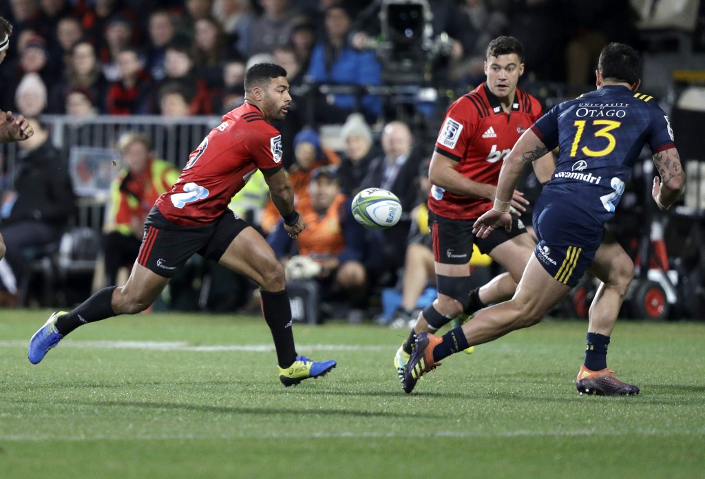 Crusaders Richie Mo'unga, left, passes the ball to teammate David Havili as Highlanders Rob Thompson, right, chases during the Super Rugby quarterfina...
