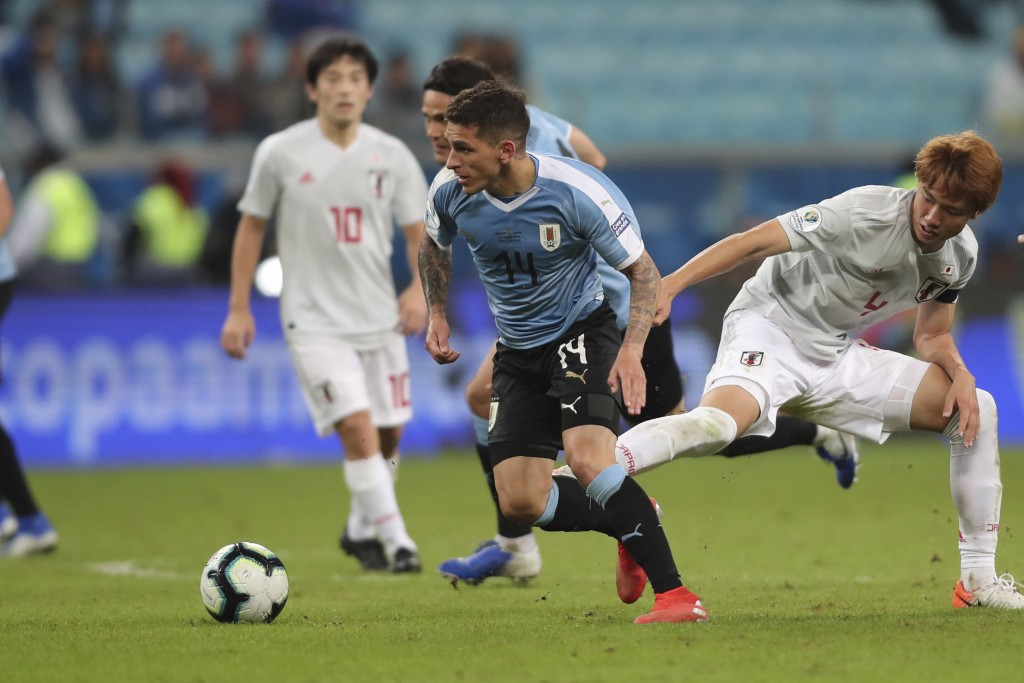 Uruguay's Lucas Torreira, center, and Japan's Kou Itakura fight for the ball during a Copa America Group C soccer match at the Arena Gremio in Porto A...