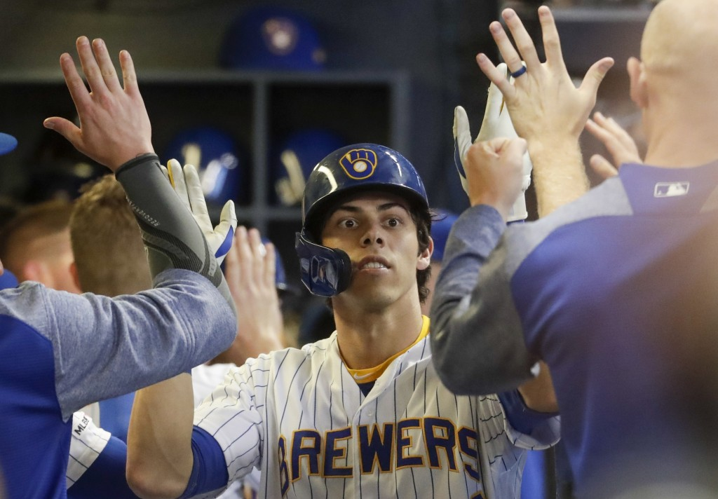 Milwaukee Brewers' Christian Yelich is congratulated after hitting a two-run home run during the fifth inning of a baseball game against the Cincinnat...