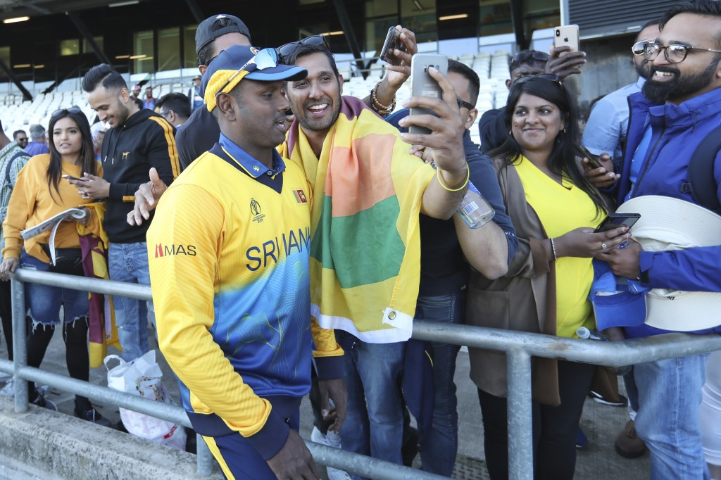 Sri Lanka's Angelo Mathews takes pictures with fans at the end of the Cricket World Cup match against England in Leeds, England, Friday, June 21, 2019...