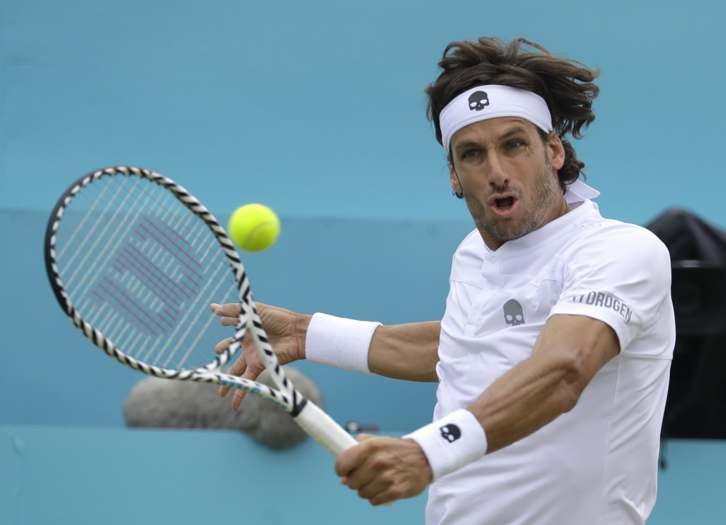 Feliciano Lopez of Spain plays a return to Milos Raonic of Canada during their quarterfinal singles match at the Queens Club tennis tournament in Lond...