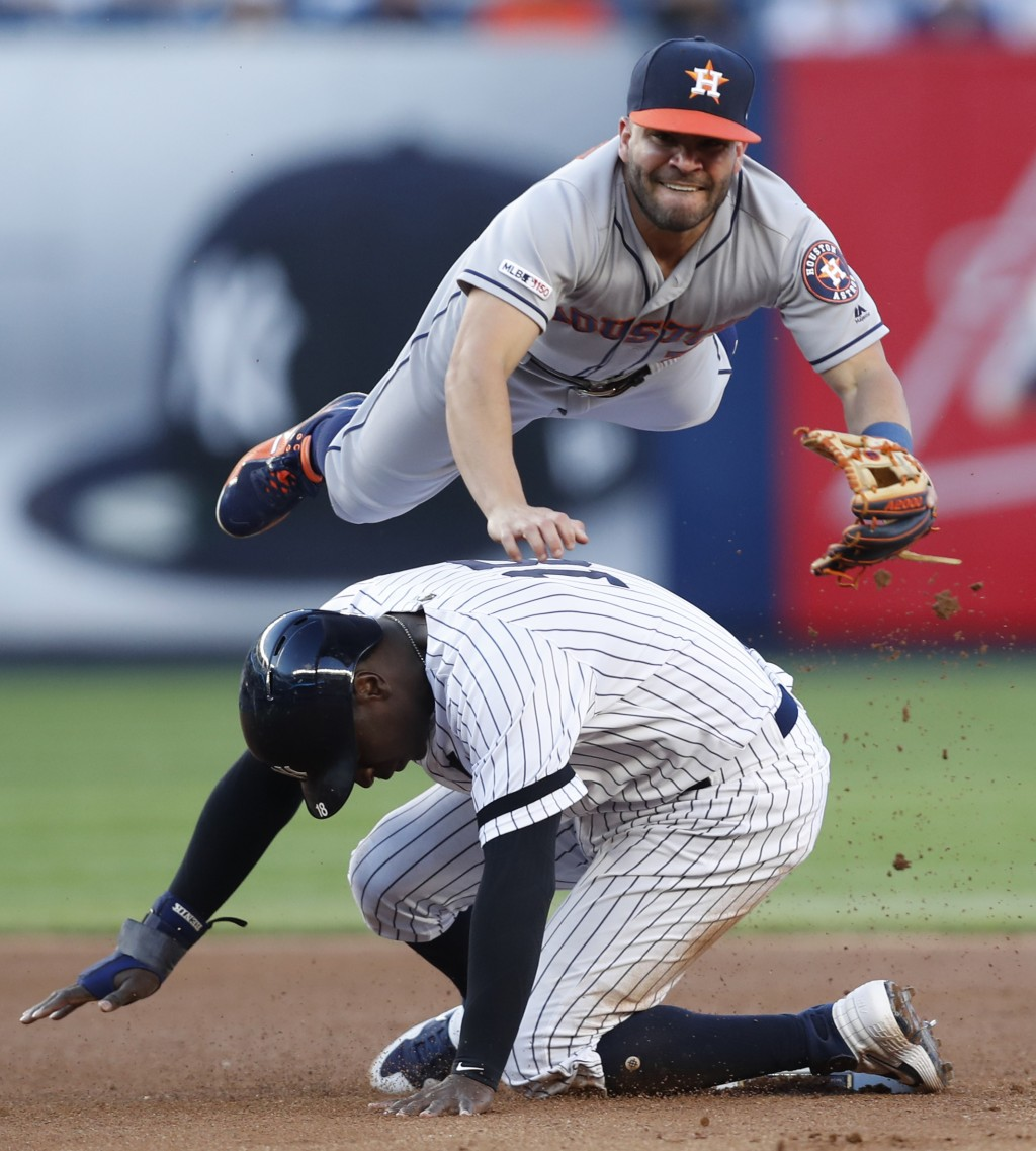 Houston Astros second baseman Jose Altuve goes over New York Yankees' Didi Gregorius (18) after throwing to first  for a double play on Giancarlo Stan...
