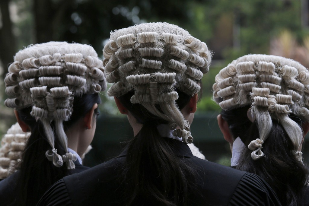 In this Saturday, June 22, 2019, file photo, barristers pose for a group photo after an appointment ceremony for senior counsel outside the Court of F...