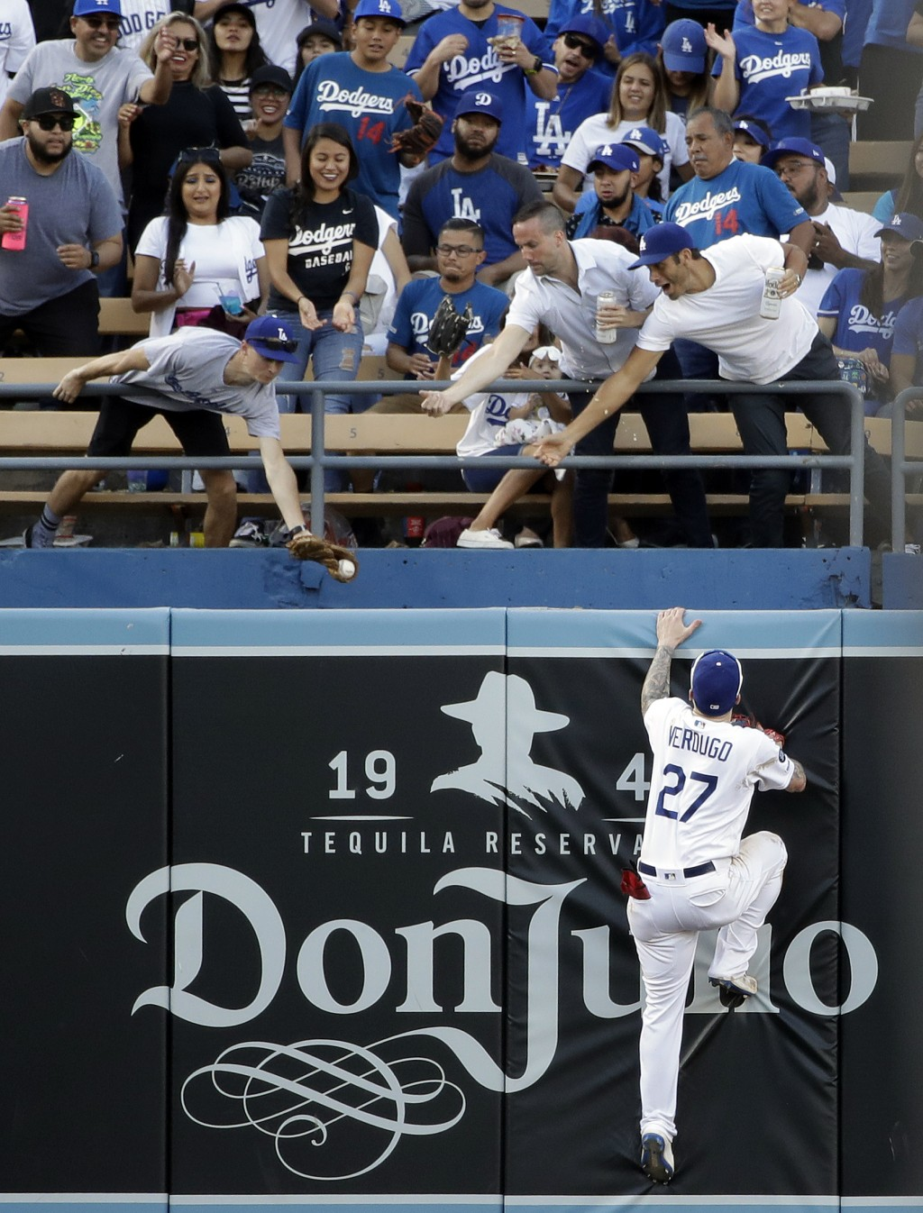 Los Angeles Dodgers center fielder Alex Verdugo, right, leaps at the wall but can't catch a solo home run from Colorado Rockies' Raimel Tapia during t...