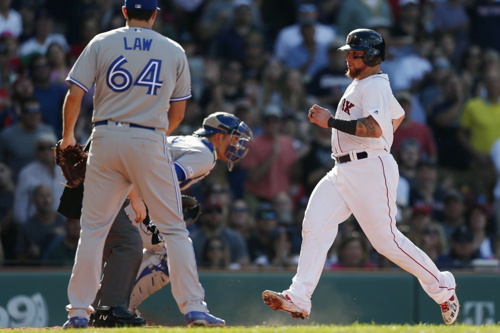 Boston Red Sox's Christian Vazquez, right, scores on a two-run double by Jackie Bradley Jr. off Toronto Blue Jays' Derek Law (64) during the second in...