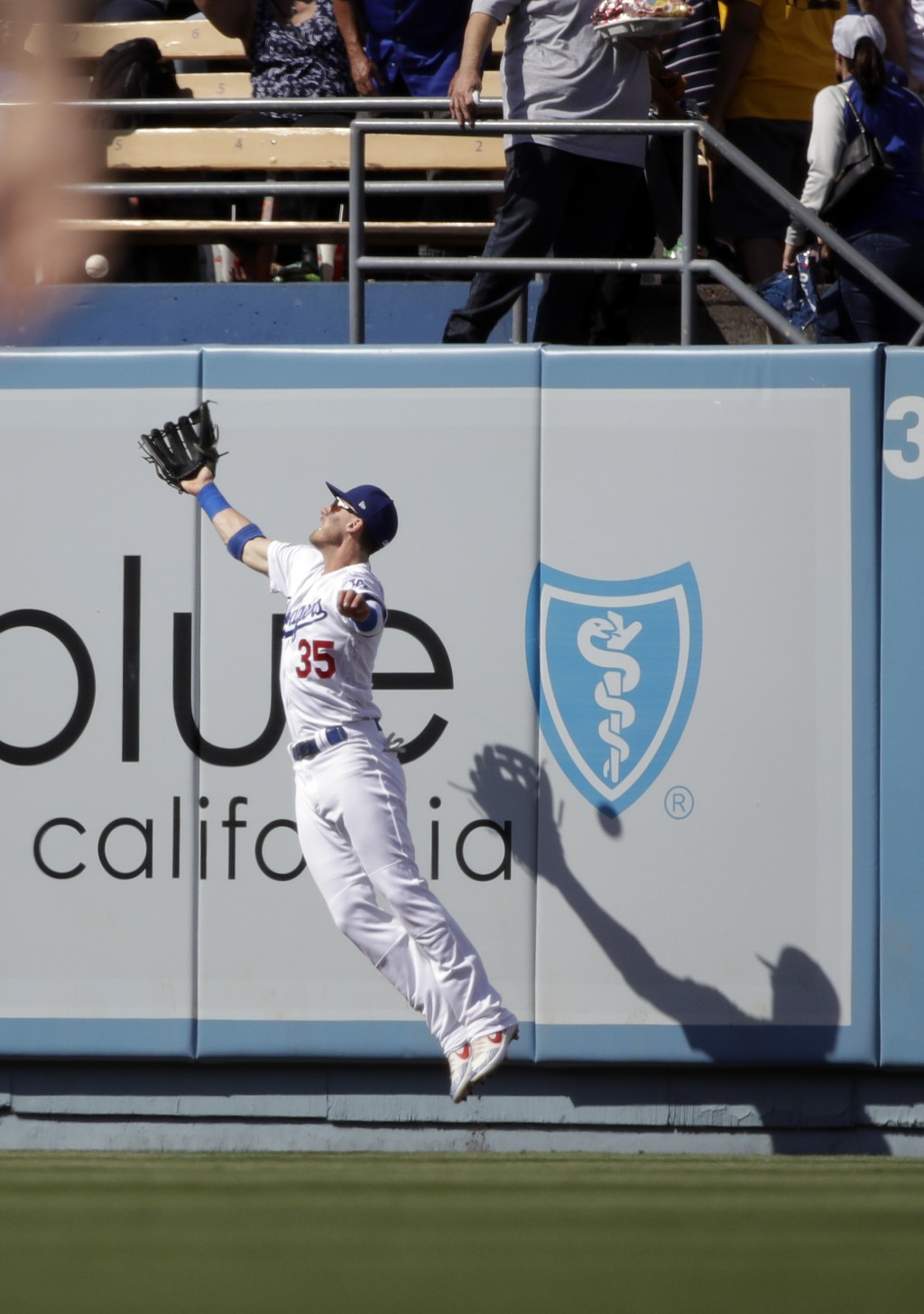 Los Angeles Dodgers right fielder Cody Bellinger makes a leaping catch on a fly ball from Colorado Rockies' David Dahl during the first inning of a ba...