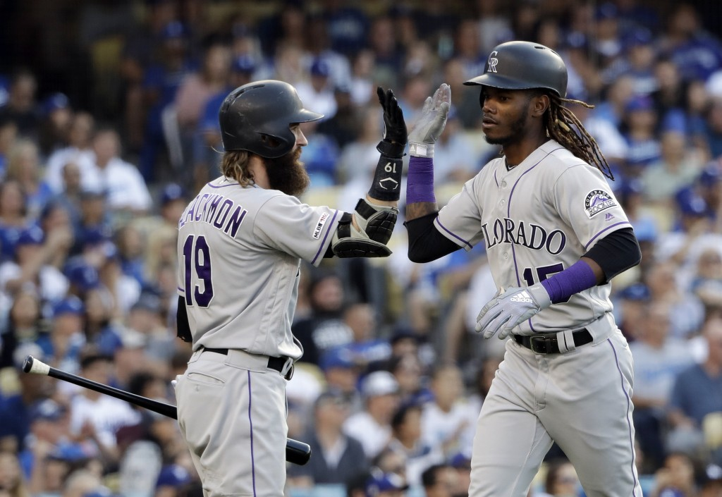 Colorado Rockies' Raimel Tapia, right, celebrates his solo home run with Charlie Blackmon during the seventh inning of the team's baseball game agains...