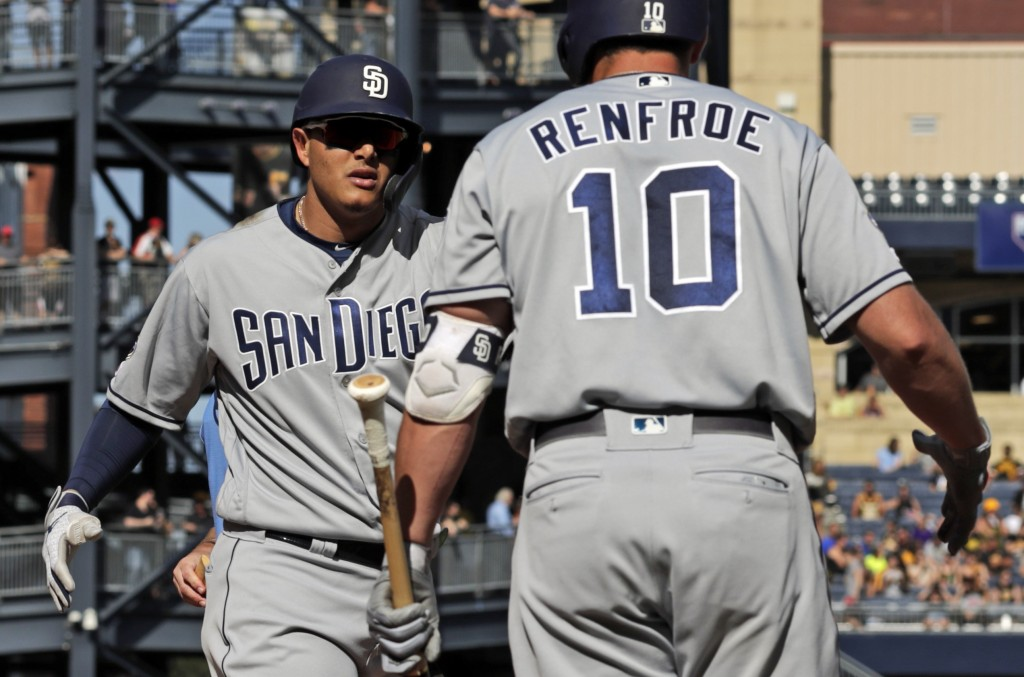 San Diego Padres' Manny Machado, left, celebrates his solo home run off Pittsburgh Pirates starting pitcher Chris Archer with Hunter Renfroe (10) duri...