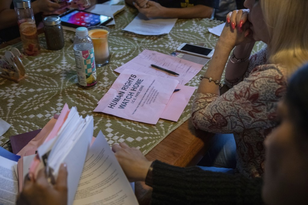 "In this Wednesday, June 19, 2019 photo, a flyer that reads  ""Human Rights Watch Home, ICE Free Zone "" rests on a table during an emergency meeting pla..."