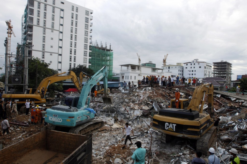 In this Sunday, June 23, 2019, file photo, rescuers try to remove the rubble at the site of a collapsed building in Preah Sihanouk province, Cambodia....