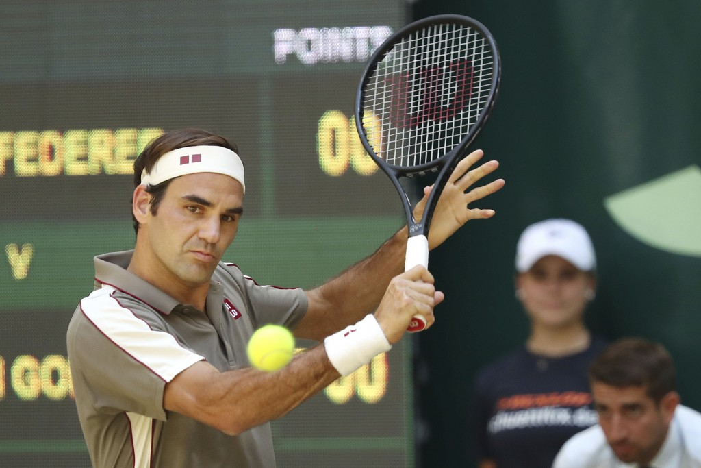 Swiss Roger Federer hits a backhand in the tennis ATP final against Belgium David Goffin in Halle, Germany, Sunday, June 23, 2019.  (Friso Gentsch/dpa...