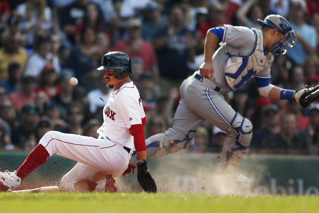 Boston Red Sox's Mookie Betts, left, scores on a two-run double by Andrew Benintendi as the ball gets by Toronto Blue Jays' Luke Maile during the seco...